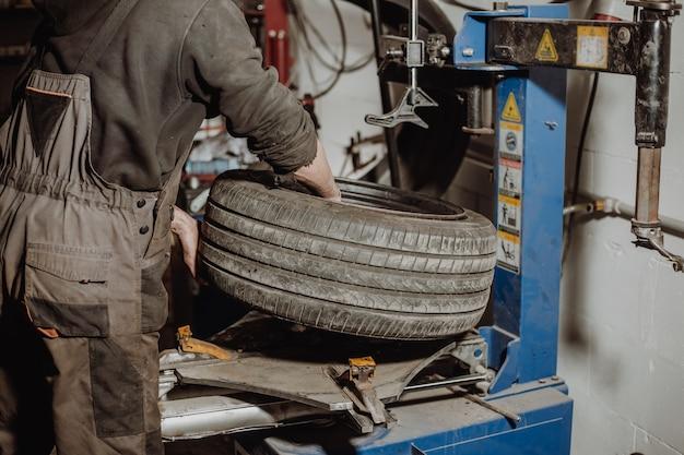 Mechanik samochodowy zdejmujący oponę z felgi za pomocą sprzętu do usuwania opon, klucz pneumatyczny odkręca koło