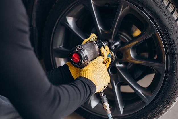 Mechanik samochodowy zmienia koła w samochodzie