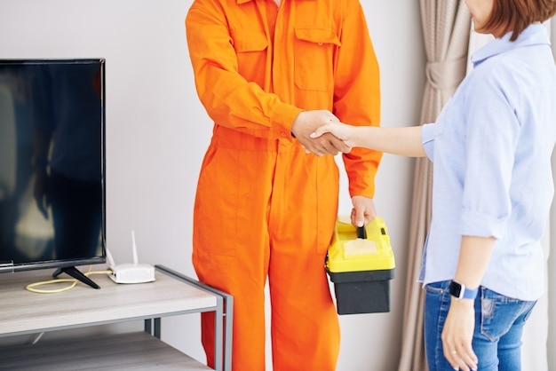 Mechanik ściskając rękę młodej kobiety po zakończeniu pracy w jej mieszkaniu