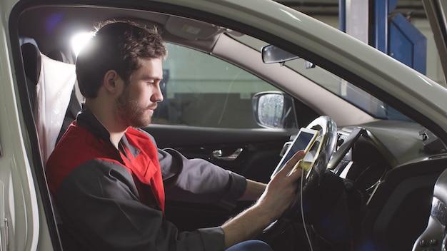 Mechanik siedzi w samochodzie robi diagnostyki na cyfrowej tablecie.