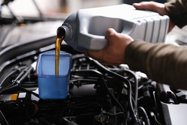 Mechanik ślusarz wlewa olej silnikowy do plastikowego pojemnika na silniku silnikowym