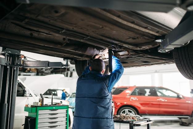 Mechanik sprawdza zawieszenie, samochód na podnośniku
