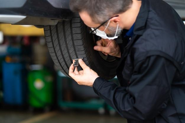 Mechanik sprawdzający głębokość bieżnika opon samochodowych. koncepcja konserwacji samochodów i serwisu samochodowego.