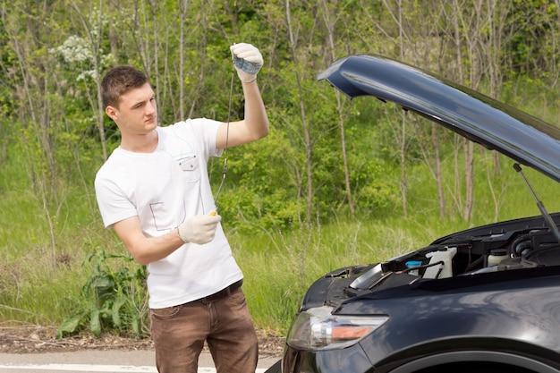 Mechanik sprawdzający poziom oleju w samochodzie
