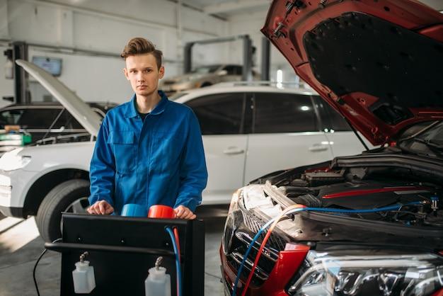 Mechanik stoi przy układzie diagnostycznym klimatyzacji. przegląd kondycjonera w serwisie samochodowym