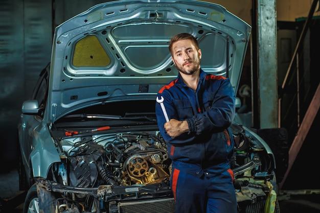 Mechanik stojący w pobliżu samochodu z otwartą maską