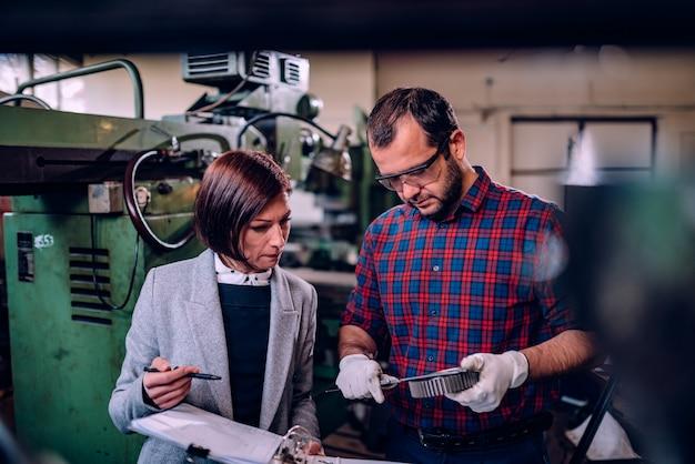 Mechanik stojący z inżynier kobiet i pomiaru średnicy koła zębatego