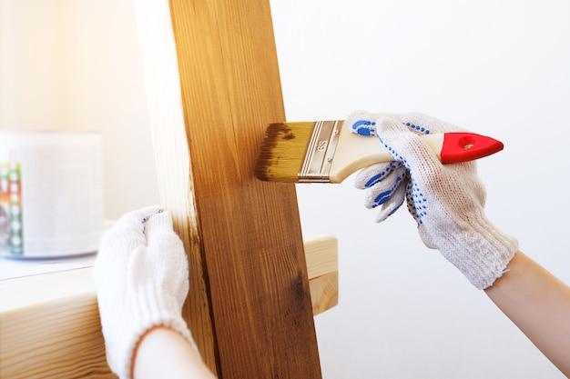 Mechanik, stolarz, ciężko pracujący stosuje lakier ochronny lub farbę na drewnianej desce.