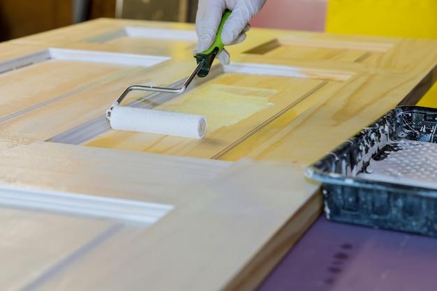 Mechanik stolarz pracujący przy malowaniu drewnianych drzwi za pomocą wałka ręcznego