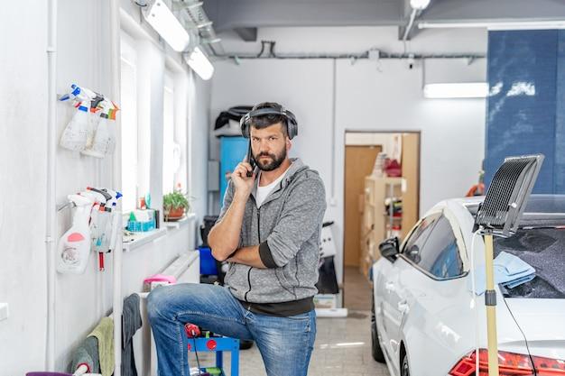 Mechanik telefonujący w garażu do ręcznego mycia i czyszczenia samochodów