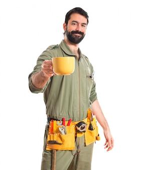 Mechanik trzyma filiżankę kawy