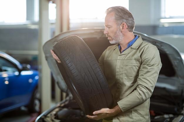 Mechanik trzyma oponę