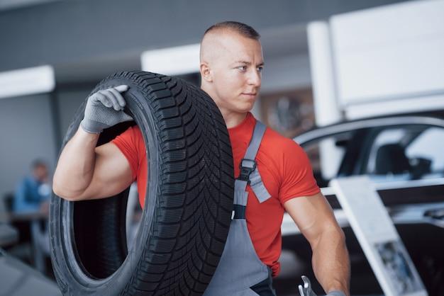 Mechanik trzyma opony oponę w garażu naprawy. wymiana opon zimowych i letnich