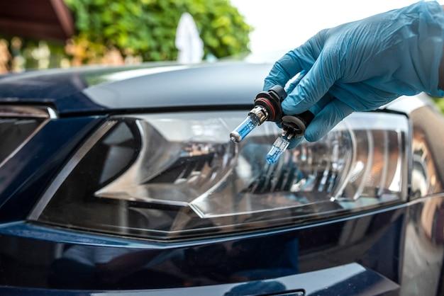 Mechanik trzyma samochodową żarówkę halogenową do naprawy przed samochodem reflektorów w tle