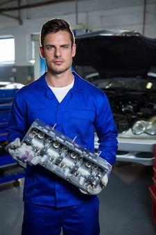Mechanik trzyma silnik samochodu