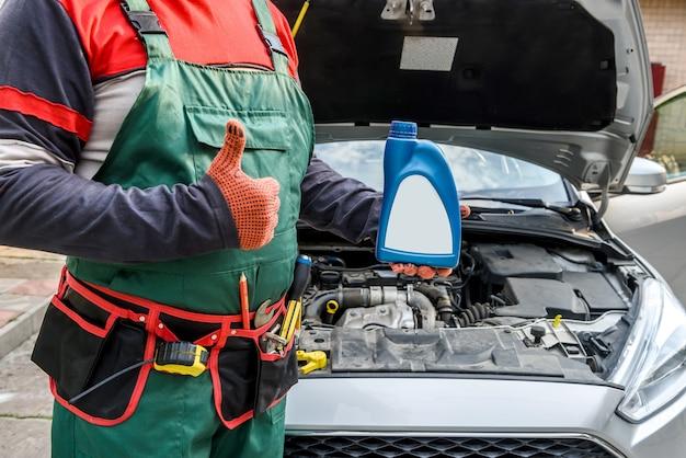 Mechanik trzymając butelki z olejem w pobliżu silnika samochodu