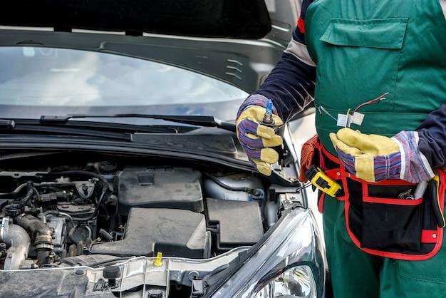 Mechanik trzymający lampę i kable od reflektora samochodu