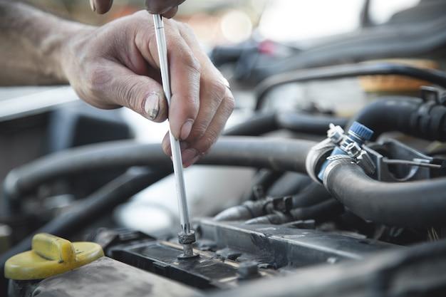 Mechanik trzymający śrubokręt. naprawa samochodów, centrum serwisowe