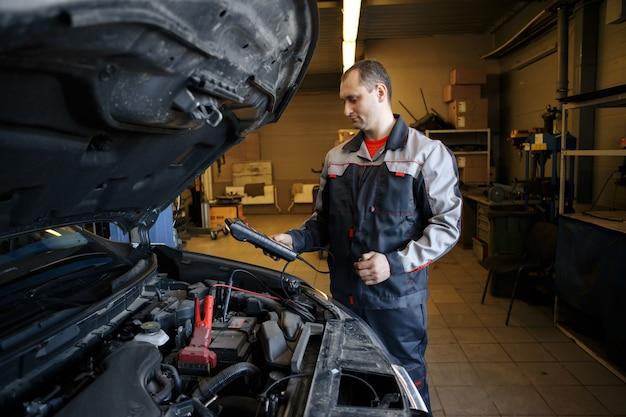 Mechanik używający kabli rozruchowych do rozruchu silnika samochodu