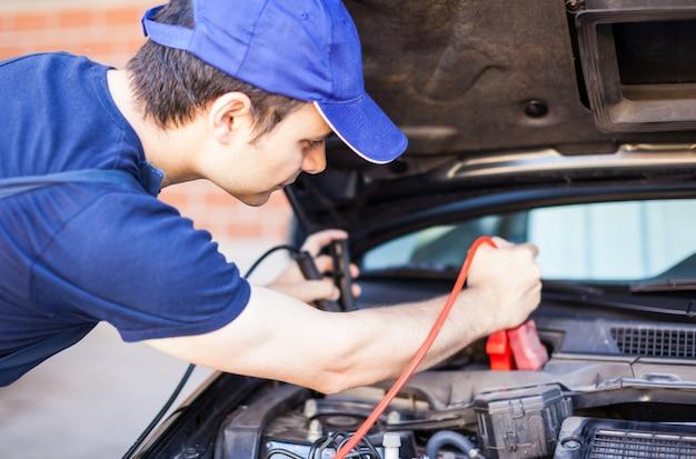 Mechanik używający kabli wspomagających do rozruchu silnika samochodu