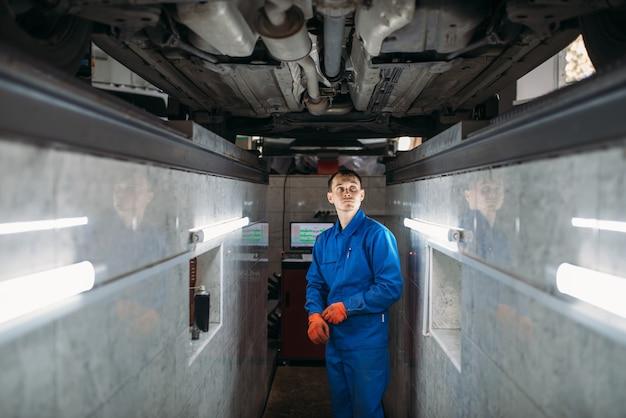 Mechanik w boksie sprawdza dno samochodu