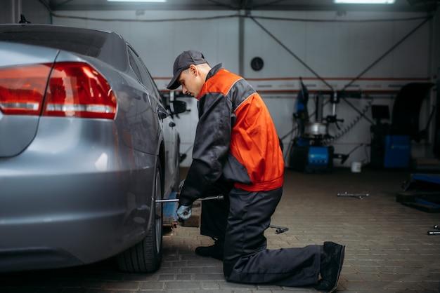 Mechanik w mundurze odkręca koło w serwisie oponiarskim. mężczyzna naprawia oponę samochodową w garażu, inspekcja samochodu w warsztacie