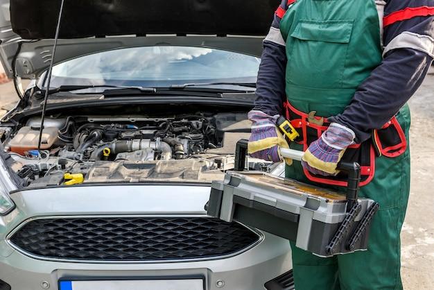 Mechanik w mundurze pozuje ze skrzynką narzędziową w pobliżu silnika samochodu