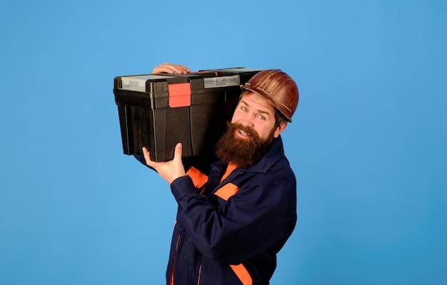 Mechanik w mundurze trzyma skrzynkę narzędziową robotnik fizyczny mężczyzna z konstruktorem skrzynek narzędziowych z pudełkiem na instrumenty