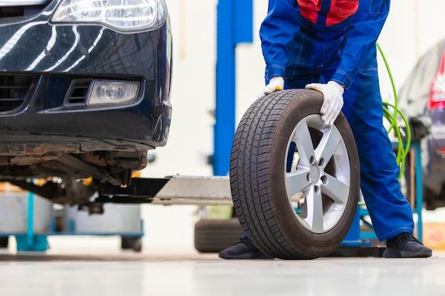 Mechanik w mundurze zmienia koła / opony podczas pracy w centrum napraw samochodów