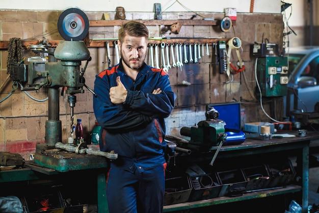 Mechanik w niebieskim kombinezonie ochronnym stoi w garażu samochodowym w pobliżu wiertarki.