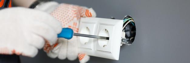Mechanik w rękawicach mocujących gniazdo za pomocą śrubokręta