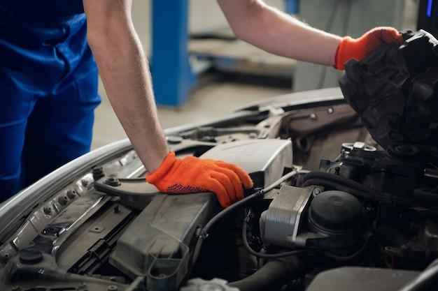 Mechanik w rękawiczkach sprawdza uszkodzony silnik samochodu. zbliżenie