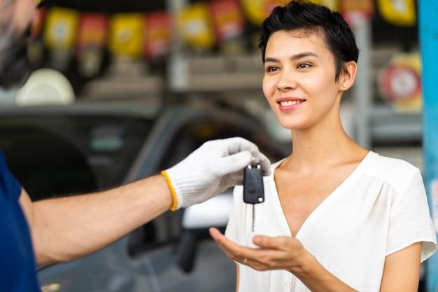 Mechanik w średnim wieku z brodą daje kluczyk klientce na stacji obsługi samochodów i w warsztacie samochodowym