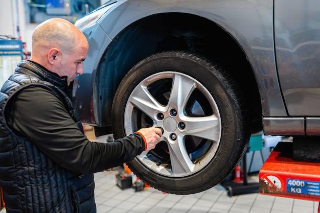 Mechanik w warsztacie samochodowym odkręcający nakrętki koła pojazdu na podnośniku automatycznym