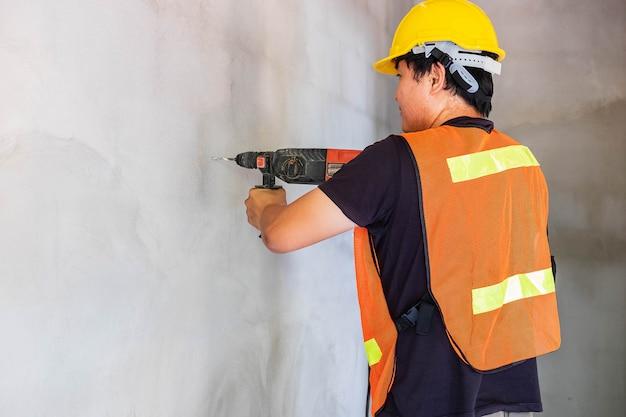 Mechanik wierci ścianę cementową.