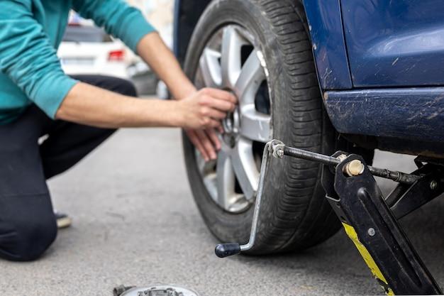 Mechanik wkręcający lub odkręcający zmieniające koło samochodowe kluczem mechanik w pracy zmieniający koło w samochodzie