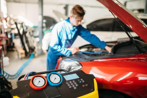 Mechanik wpompowuje freon do układu klimatyzacji samochodu. przegląd kondycjonera w serwisie samochodowym