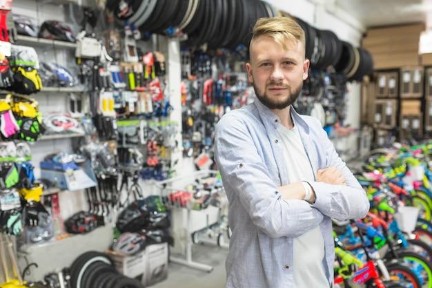 Mechanik z fałdowymi rękami stoi w rowerowym warsztacie