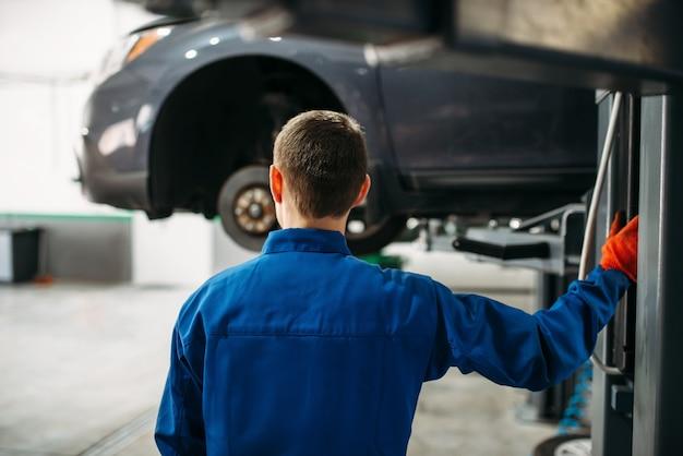 Mechanik z kluczem patrzy na samochód na podnośniku