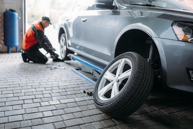 Mechanik z kluczem pneumatycznym odkręca koło w serwisie opon. mężczyzna naprawia oponę samochodową w garażu, samochód na podnośniku, przegląd w warsztacie
