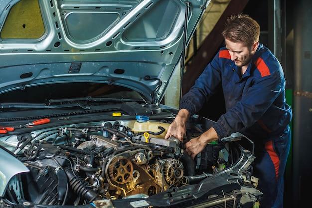 Mechanik z kluczem pracuje i naprawia samochodowy silnik w samochodowym centrum obsługi.
