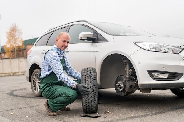 Mechanik z kołem zapasowym i zepsutym samochodem