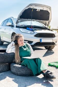 Mechanik z laptopem diagnozujący zepsuty samochód na poboczu drogi