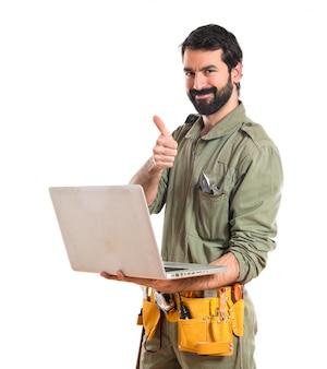 Mechanik z laptopem na białym tle