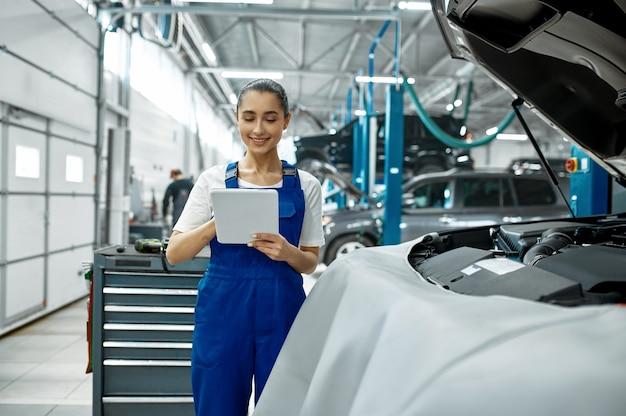 Mechanik z laptopem sprawdza silnik, serwis samochodowy, profesjonalny diagtostic