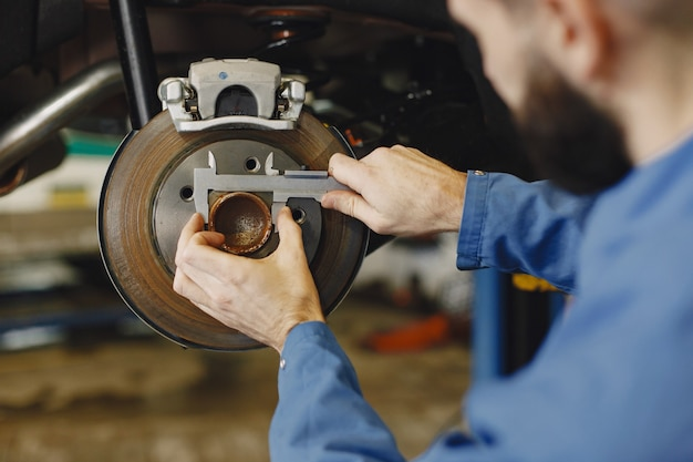 Mechanik z narzędziem. koło w rękach mechanika. niebieska odzież robocza.