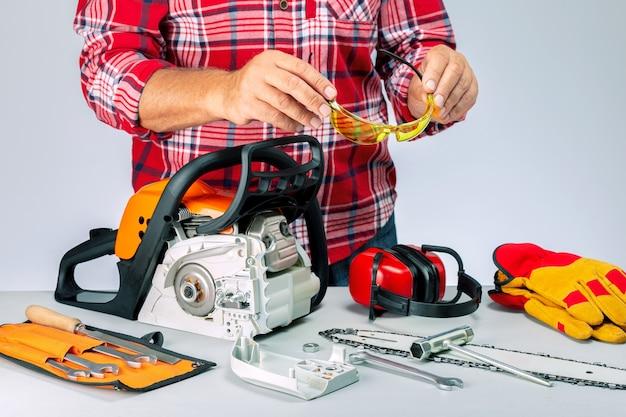 Mechanik z przemysłową odzieżą ochronną i narzędziami. serwisant naprawia piłę łańcuchową w warsztacie.