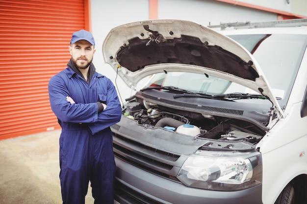 Mechanik z założonymi rękami stojący przed furgonetką