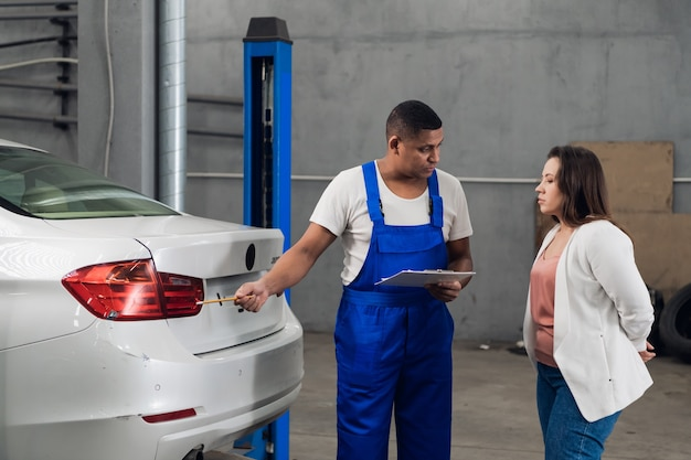 Mechanik ze schowkiem omawia z kobietą naprawę samochodu