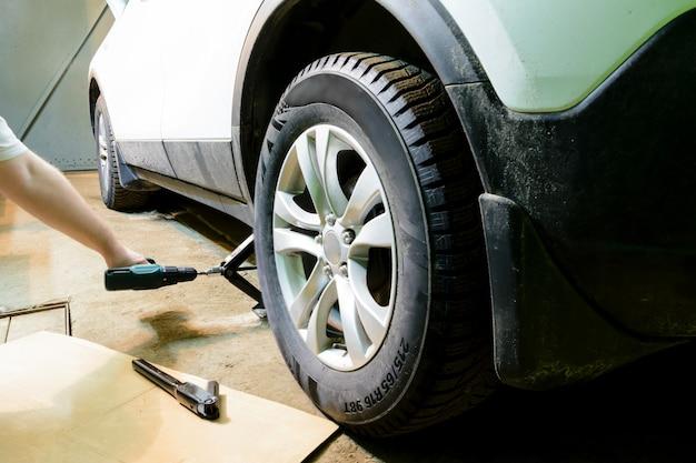 Mechanik zmienia koło samochodu w garażu. mężczyzna wymienia oponę. serwis opon. montaż opon.